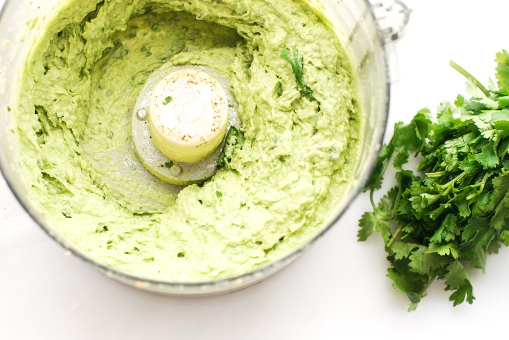 Blended tahini, avocado and peas in a food processor.