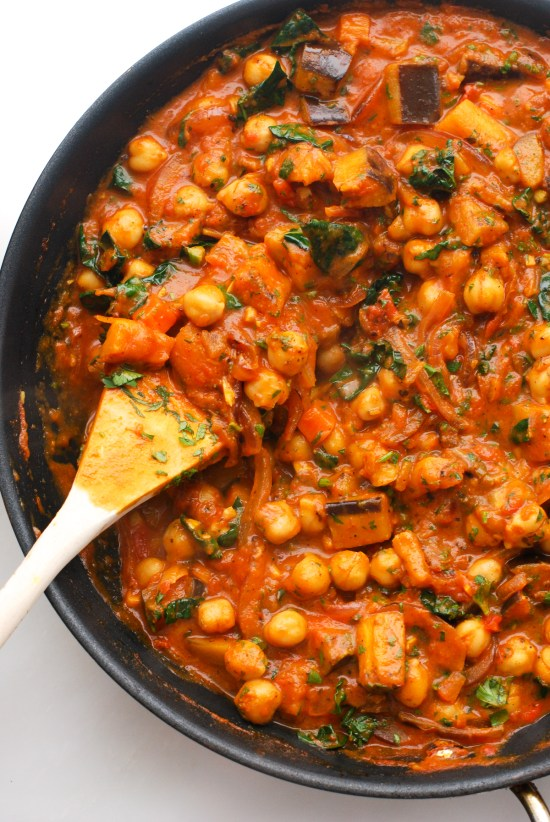 Overhead shot of a skillet filled with chickpeas, kale and eggplant simmered in a curried tomato sauce.