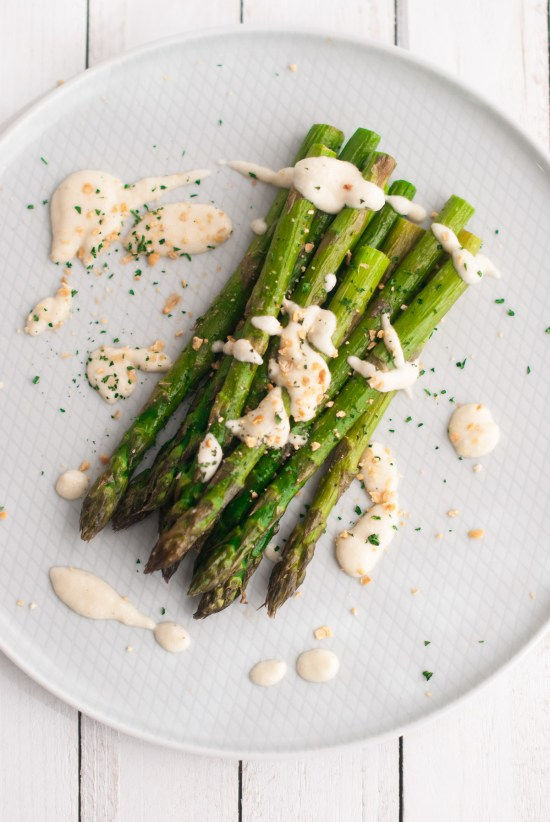 Overhead shot of a plate of roasted asparagus topped with a drizzle of creamy, cauliflower alfredo sauce, chopped parsley and crunchy breadcrumbs.