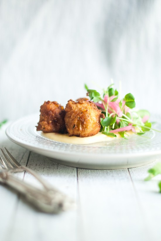 Photo of a beaded plate with pepper jack cheese fondue topped with three corn and beer fritters along with baby radish greens and pickled red onions