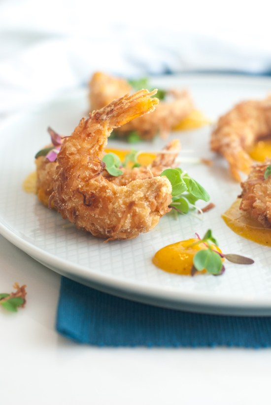 Coconut crusted shrimp arranged on a plate with bright orange mango-pepper sauce and micro greens.