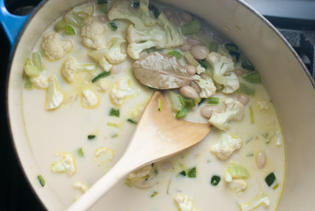 A pot of cauliflower, leeks, poblanos, stock and cream simmering on the stove.