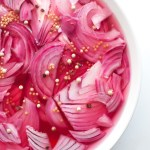 Bowl of bright pink red onions sitting in pickling liquid.
