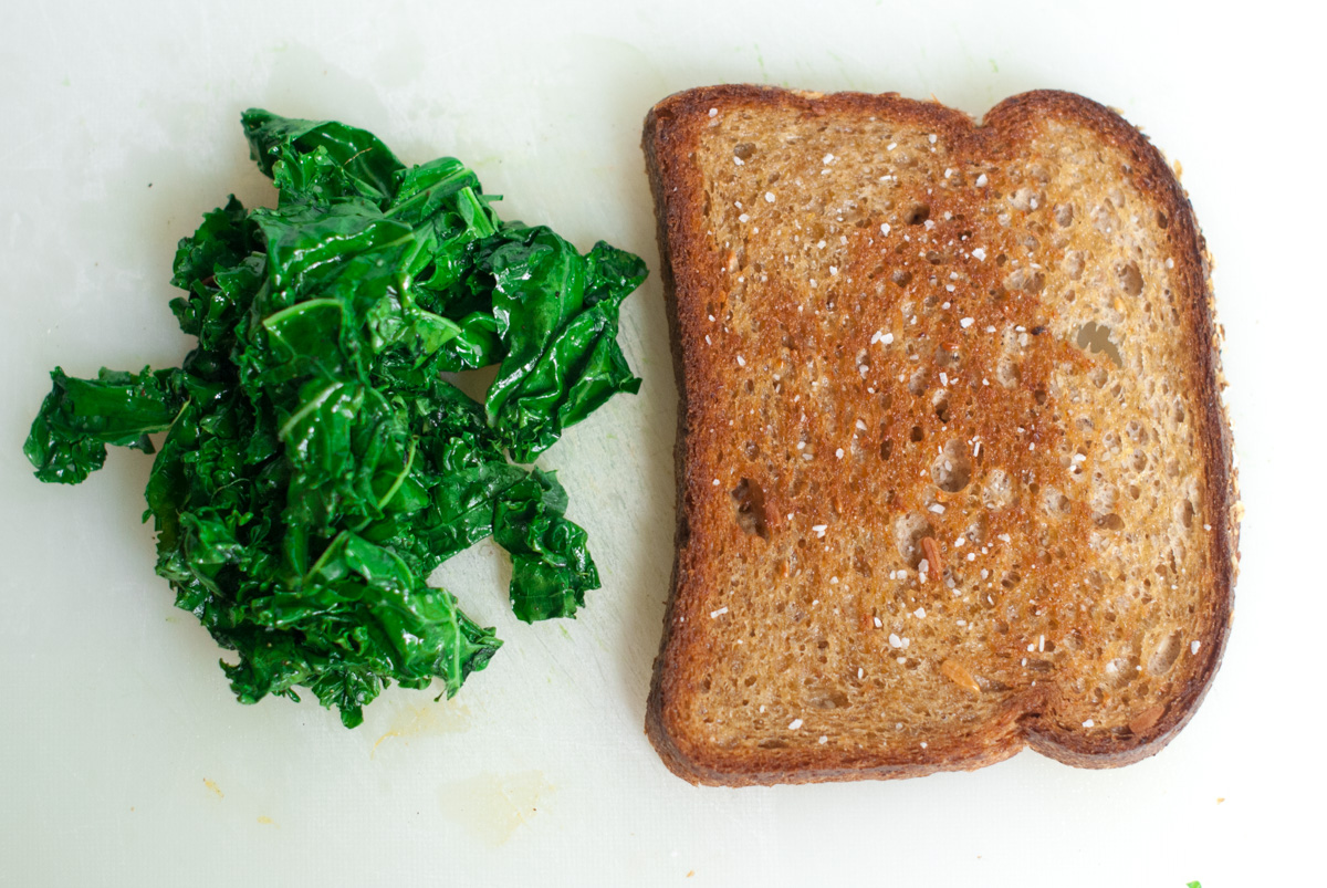 One slice of whole grain toast and a pile of sautéed kale.