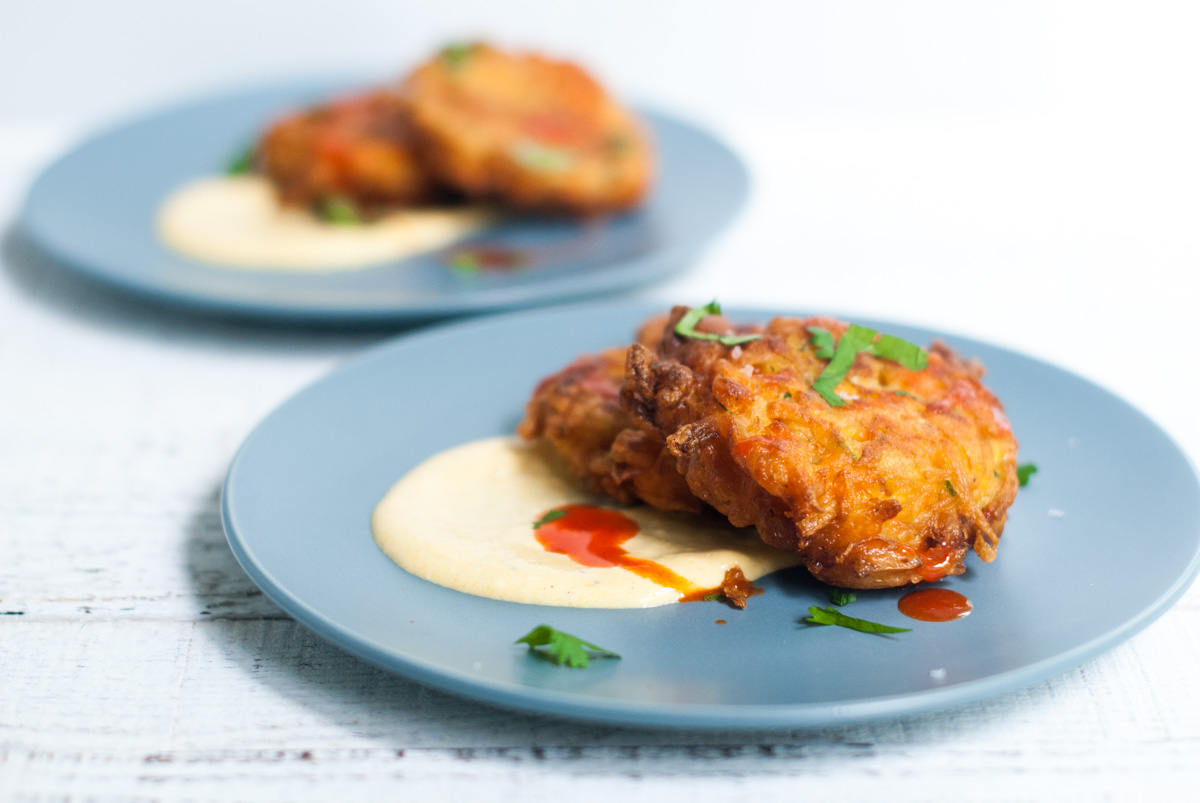Carrot Zucchini Fritters on a Blue Plate with Swirl of Mango-Pepper Cream