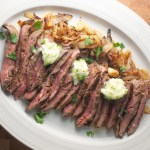 An oval platter filled with sliced flank steak, garnished with caramelized onions and topped with dollops of butter.
