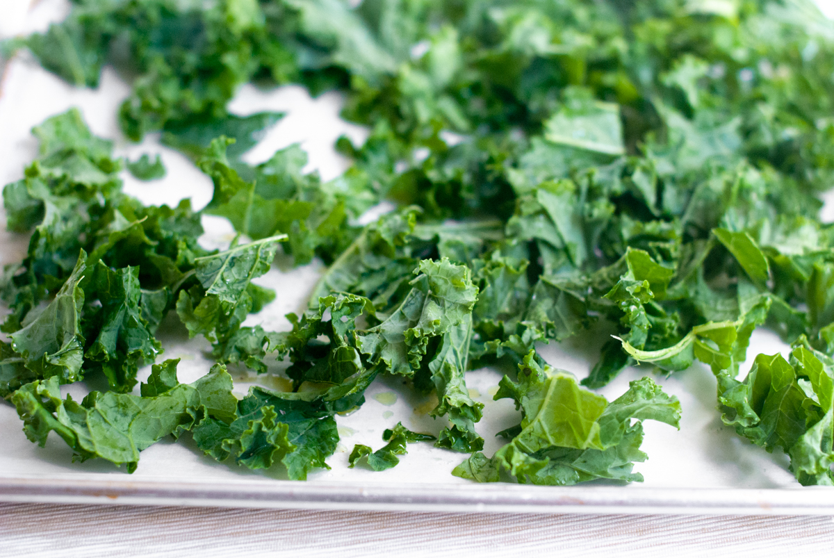 Torn leaves of kale on a sheet tray, ready for baking.