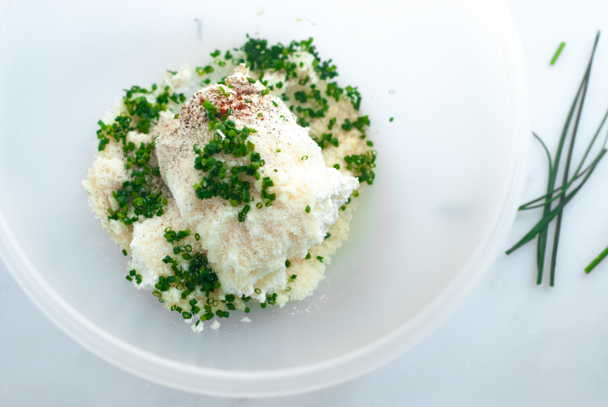 Bowl of ricotta, Parmesan, chives and cayenne ready to be mixed together and tossed with pasta.
