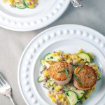 An overhead shot of a white plate with a creamy sauce of corn, zucchini and pancetta on the bottom and two seared scallops on top.