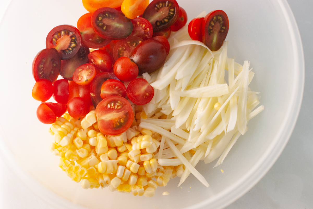 A bowl of ingredients including corn kernels, cherry tomatoes and sliced fennel.
