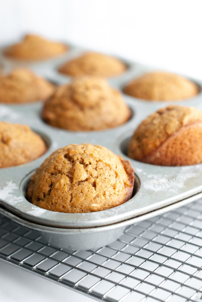 A buttered and floured muffin tin with sweet potato and almond butter muffins after baking - golden brown, and domed on top.
