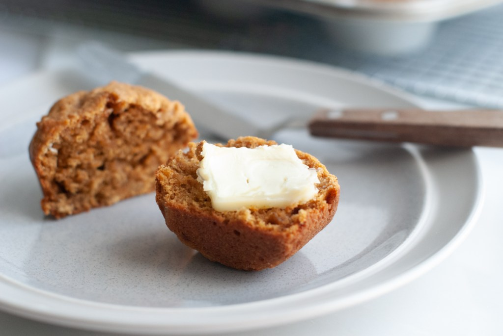 A sweet potato and almond butter muffin that's been cut in half and spread with creamy butter.