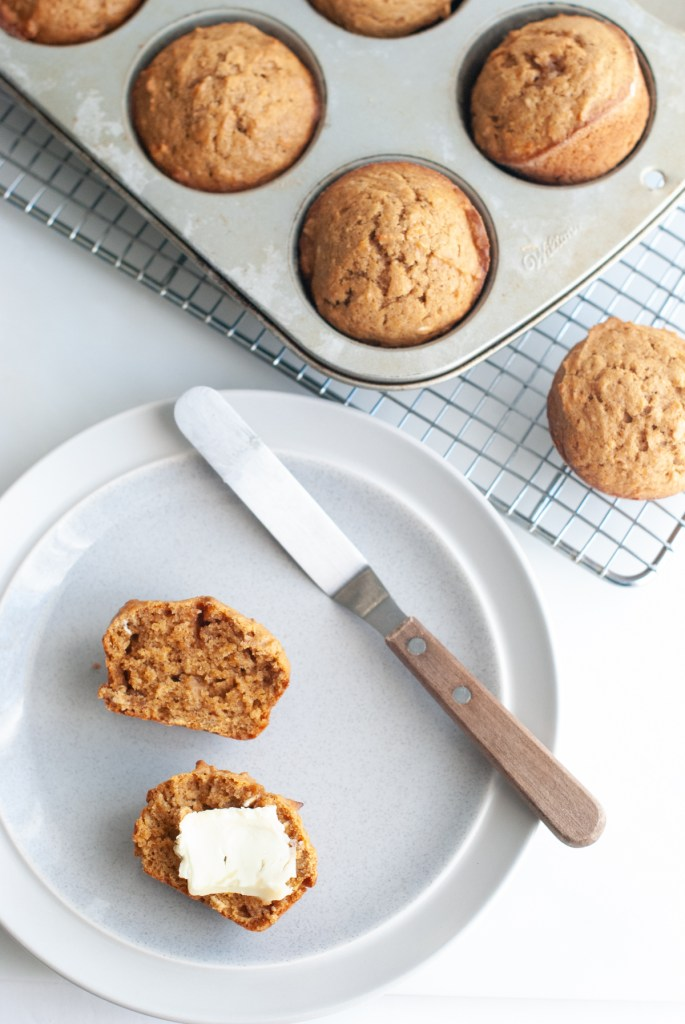 Sweet Potato and Almond Butter Muffins photographs in the tin and on a plate. Muffin cut in half and spread with creamy butter.