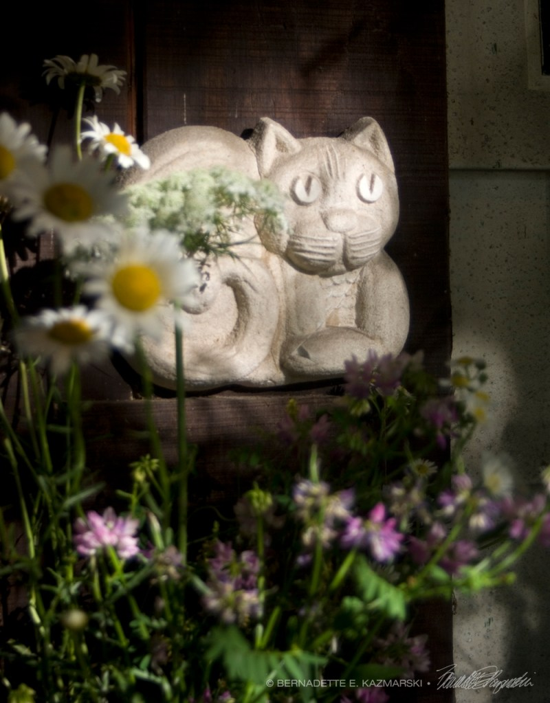 cat sculpture and flowers