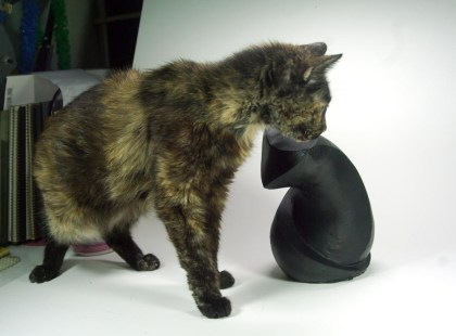 tortie cat with sculpture