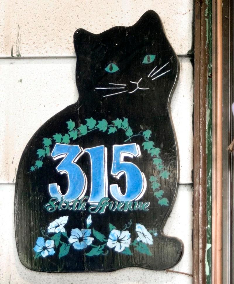 sign shaped like a black cat