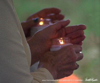 Two people hold lit candles as we recite the release for our pets.