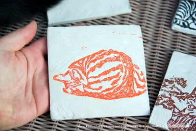 "Air-dry clay tile, ""Fawnball"" in orange."