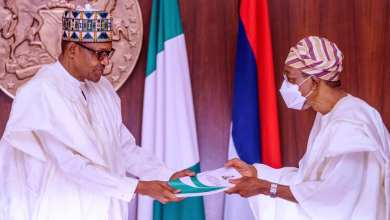 Buhari receiving the report from Aregbesola
