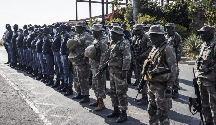 South African National Defence Forces (SNADF) soldiers and South Africa Police Services (SAPS) members line up in front of the Phoenix Police Station in Durban, on July 21, 2021 (Photo credit: AFP)