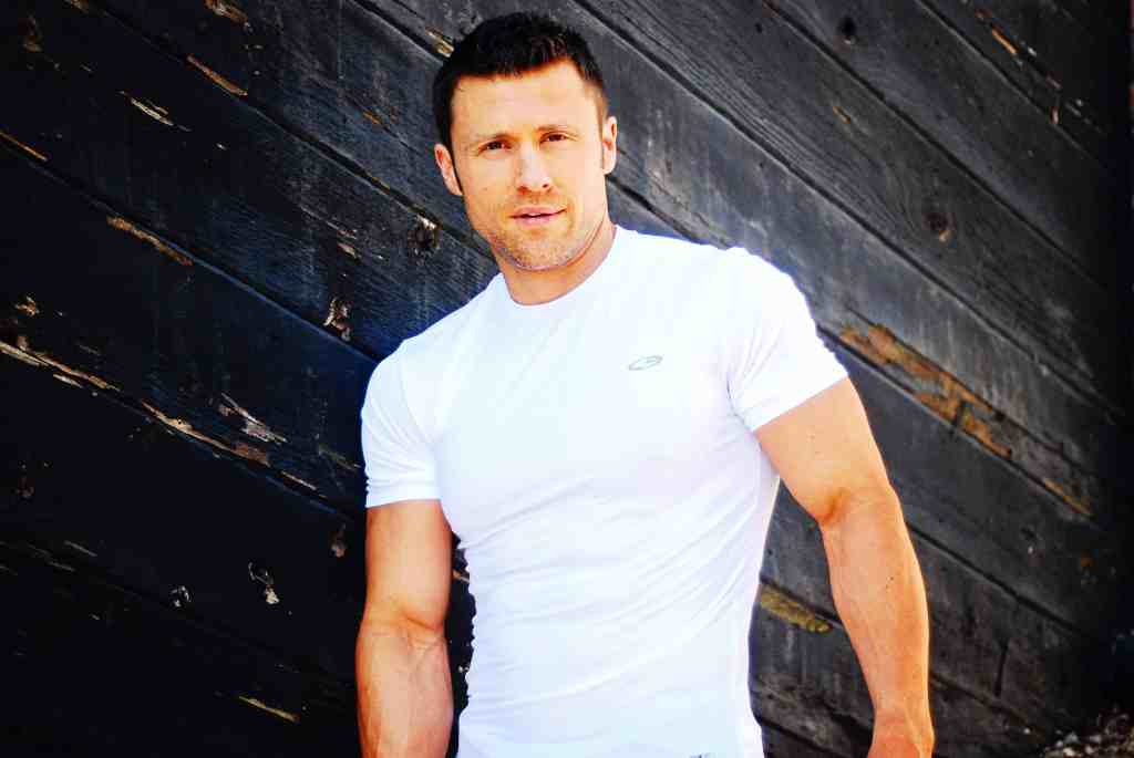 Personal trainer JC Cross in front of wood wall