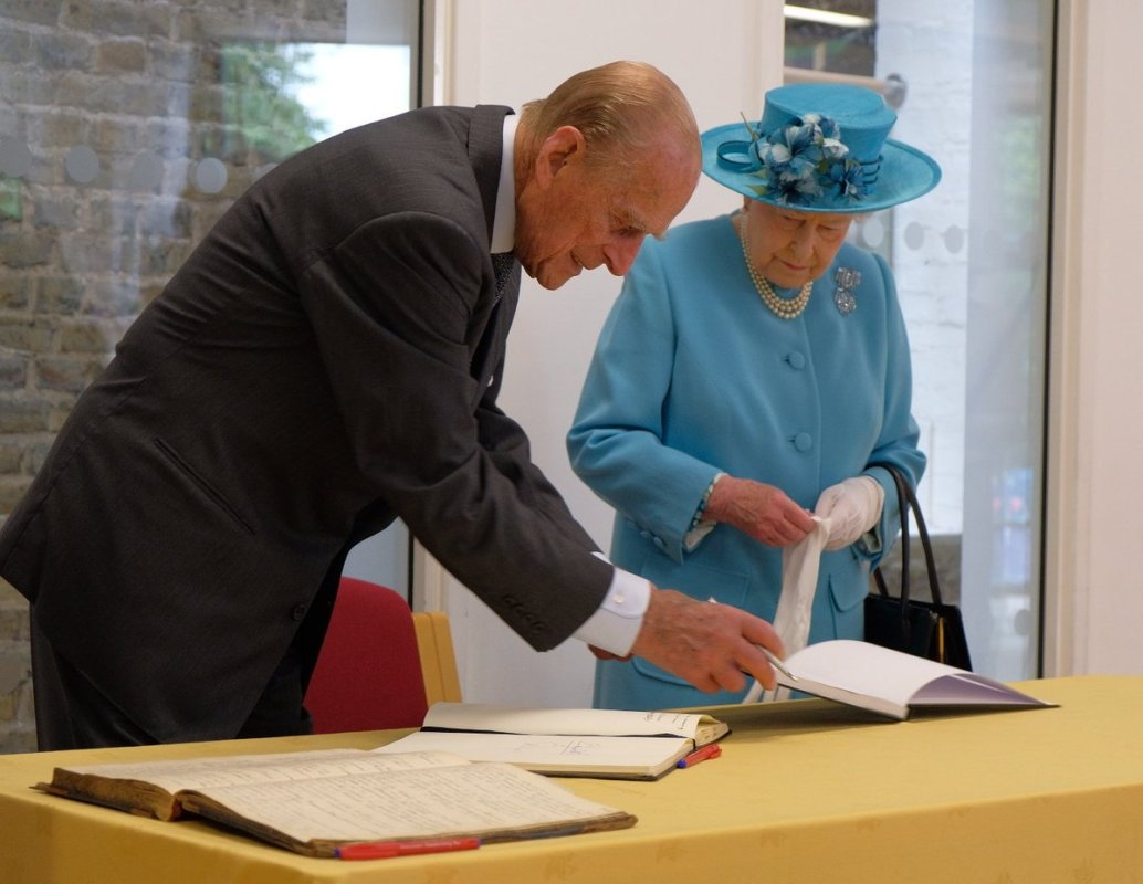 The Queen and Prince Philip sign the visitor's book at Mayflower Primary School, which was bombed in WWII, then called Upper North Street School (Royal Family)