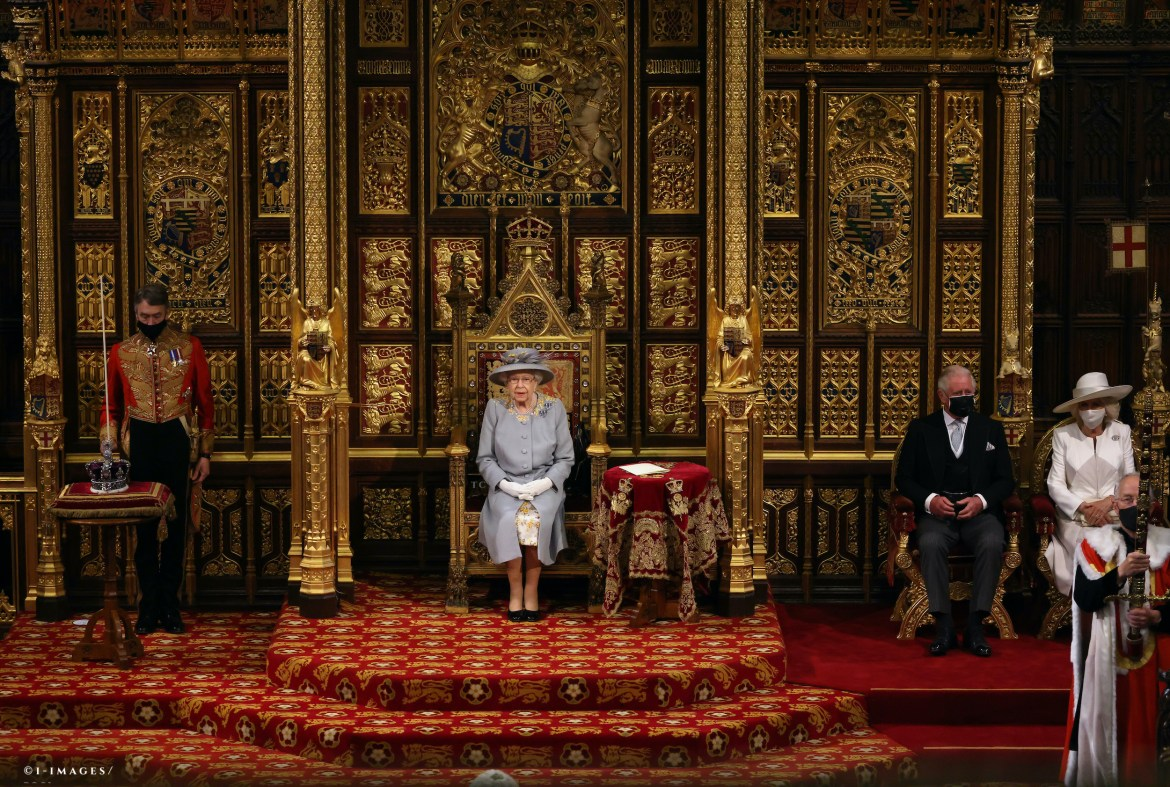 wide angle showing queen sitting on a raised throne in the house of lords, with a small side table with red velvet cloth next to her, that also holds her speech. she wears dove grey; prince charles and camilla sit on a lower part of the platform to her left.