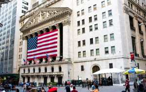 Photo of the NYSE front entrance with US flag draped over the columns