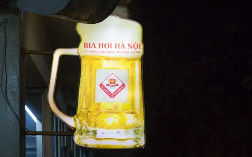 Street sign shaped like a pint of beer with red letters advertising or Bia Hoi Ha Noi (Vietnamese fresh beer)