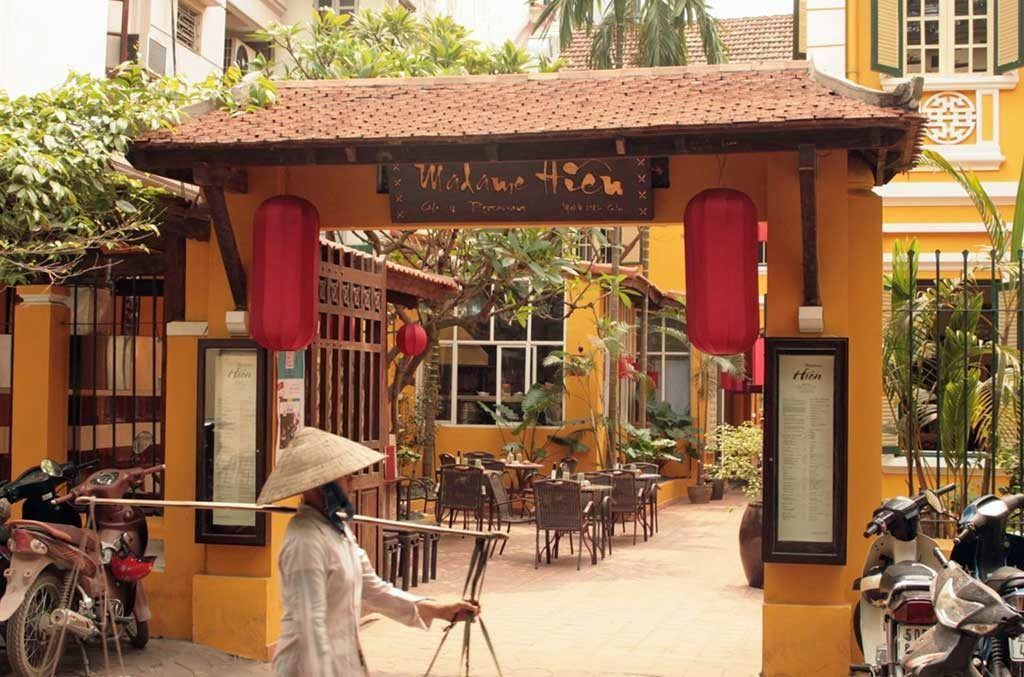 Entrance to Madame Hien, a restaurant serving some of the best food in Hanoi, Vietnam. There is an orange arch leading to an inner courtyard with tables and chairs. A woman in traditional Vietnamese clothing is walking past the entrance.