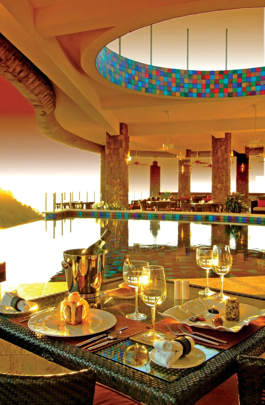 Restaurant table next to an infinity pool with a view of the sunset