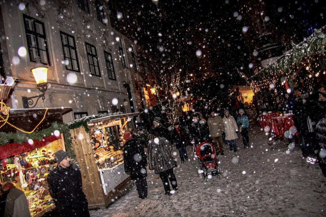 Snow falling at night at the Spittelberg Christmas Market in Vienna