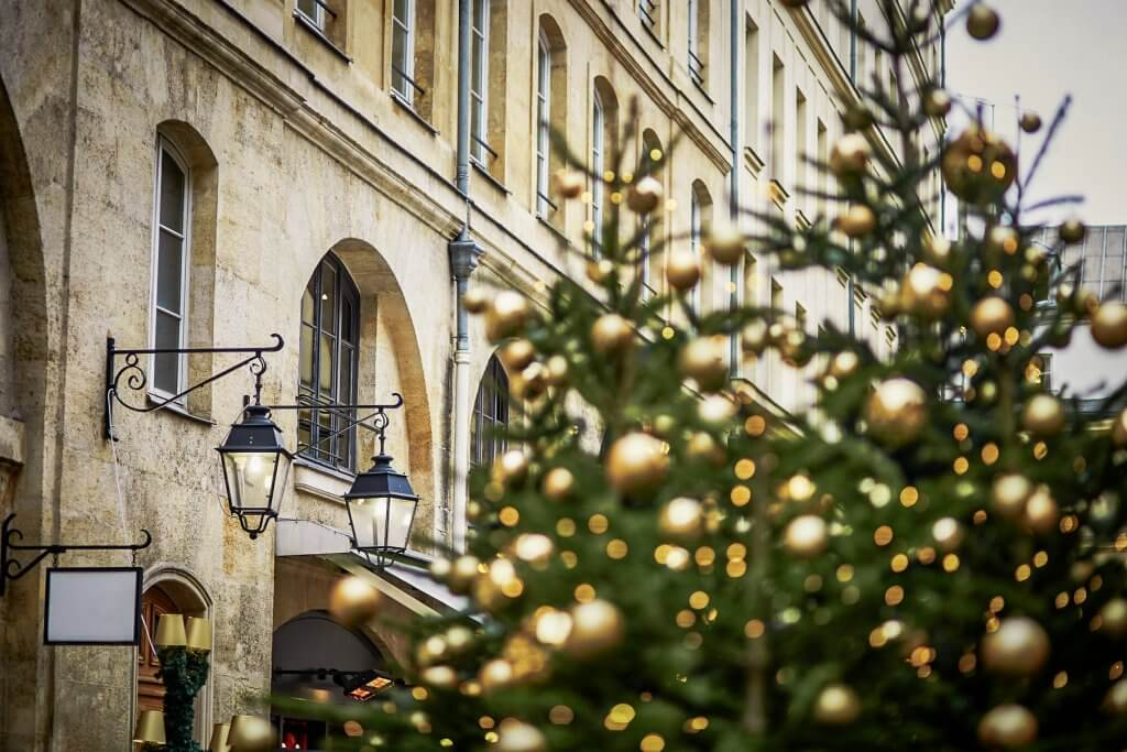 Christmas trees decorated with golden balls on a street of Paris. Seasonal winter holidays concept