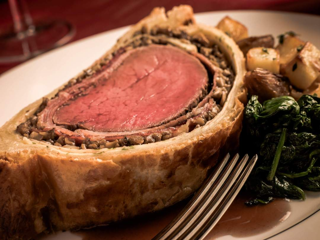 a slice of beef wellington on a plate with vegetables on the side
