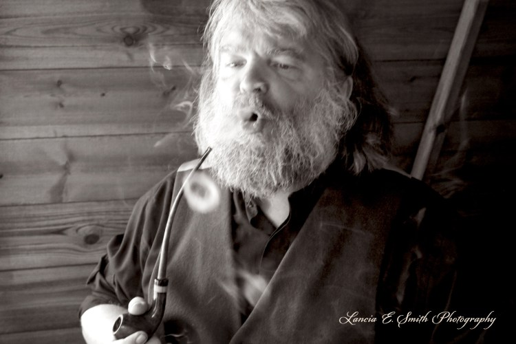 Malcolm Guite blowing smoke rings, sepia wm Image (c) Lancia E. Smith