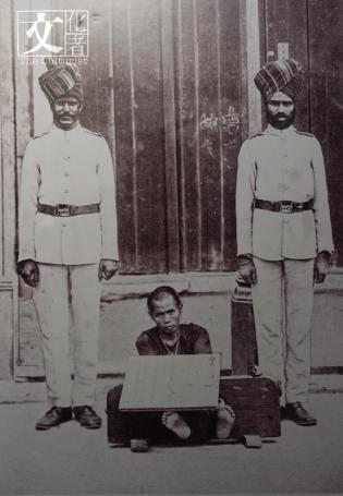 印度藉警察與被扣上腳枷的華藉犯人。(政府檔案處提供)