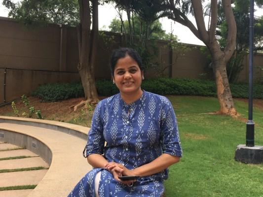 Savita sitting in a garden spot.