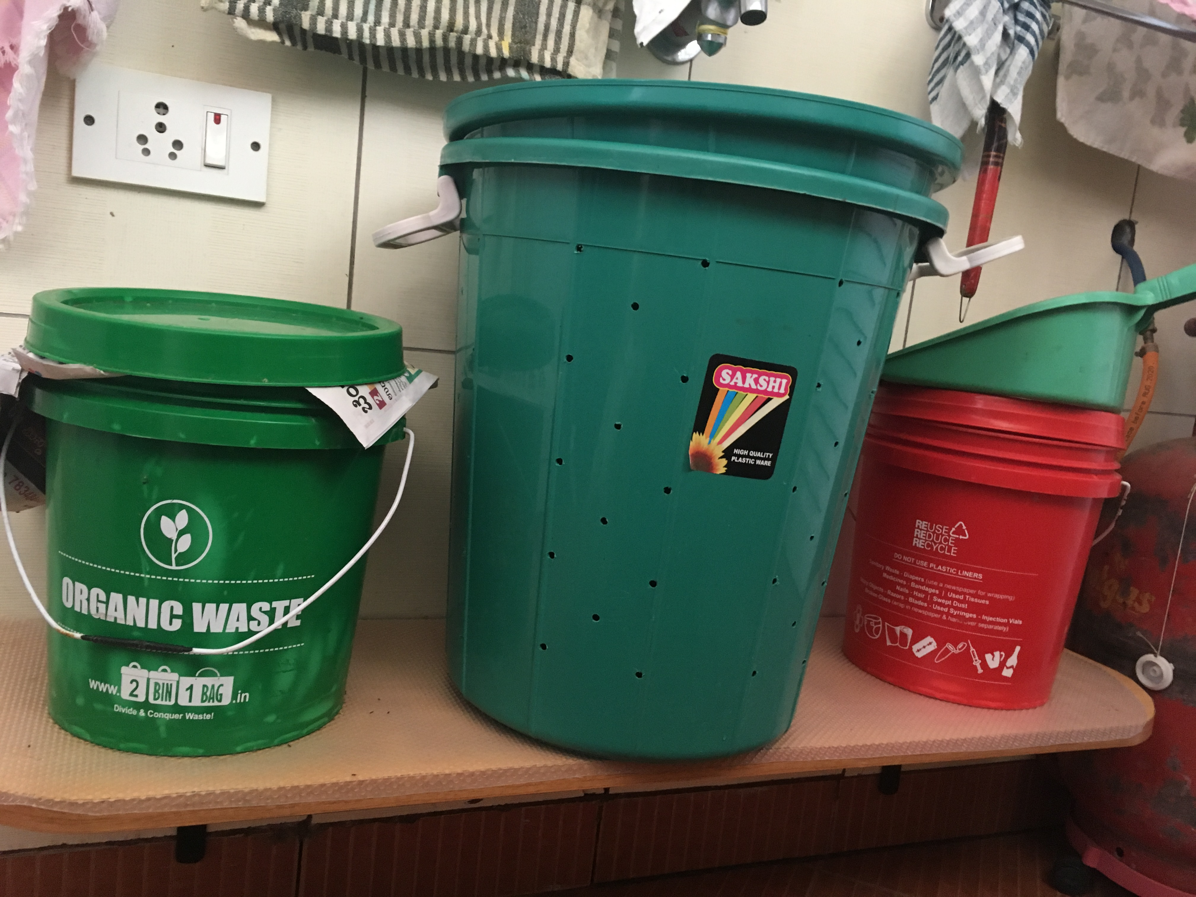 Large bins in green colour and one in red on the side.