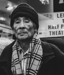 Launch feature photograph by @the_street_chimp. Black and white street portrait of Asian man wearing a hat and a checkered scarf