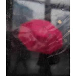 Launch feature photograph by @simonescarano.street. Abstract street photograph in colour of a person holding a red umbrella