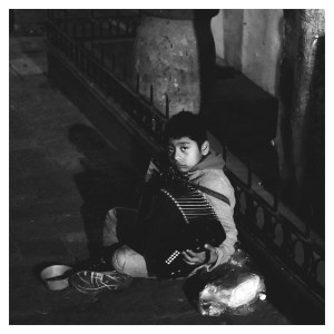 Launch feature photograph by @ikigai_street. Black and white candid street portrait of child holding accordion.