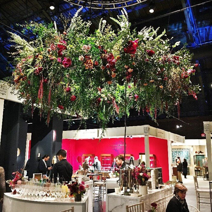 a large floral arrangement hanging above a bar at the Winter Antiques Show