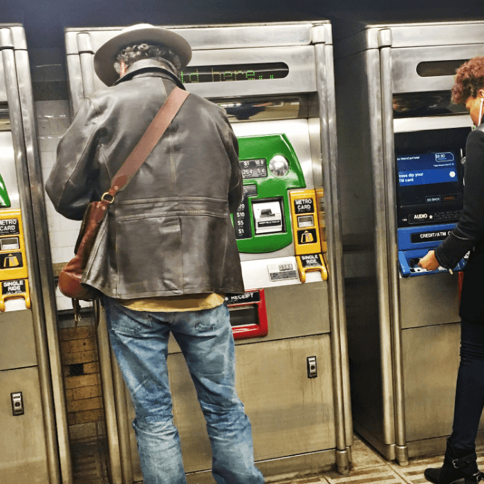 Man in leather jacket wearing a hat at the metrocard vending machine