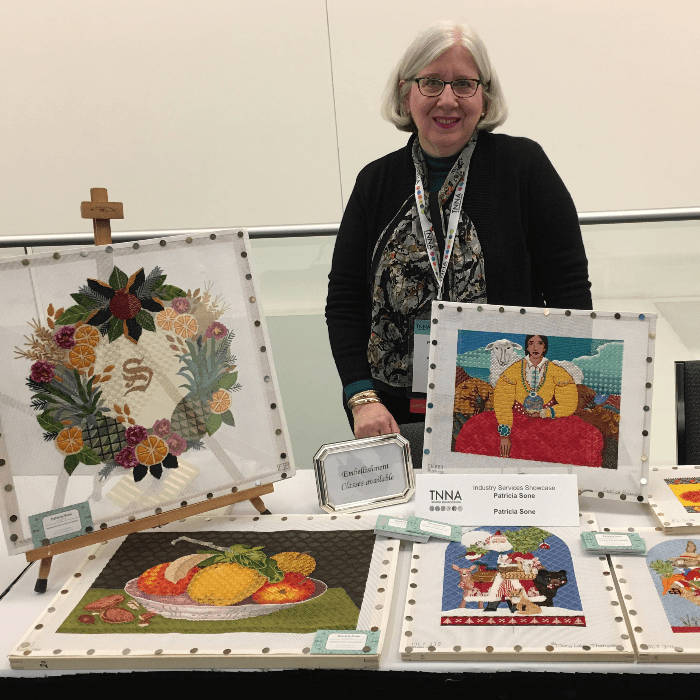 Patricia Sone with several needlepoint canvas designs