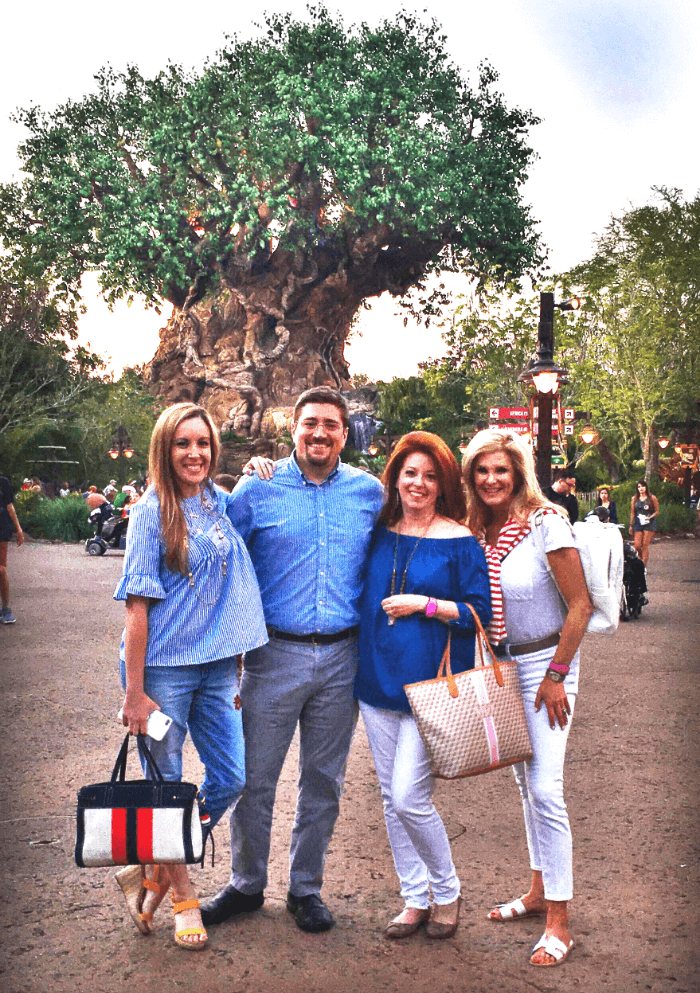 Three woman and one man standing in front of the giant Baobab tree at Disney's Animal Kingdom