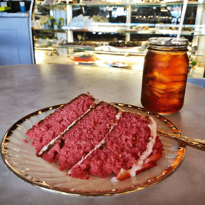 A slice of strawberry cake on a white plate next to a glass of iced tea