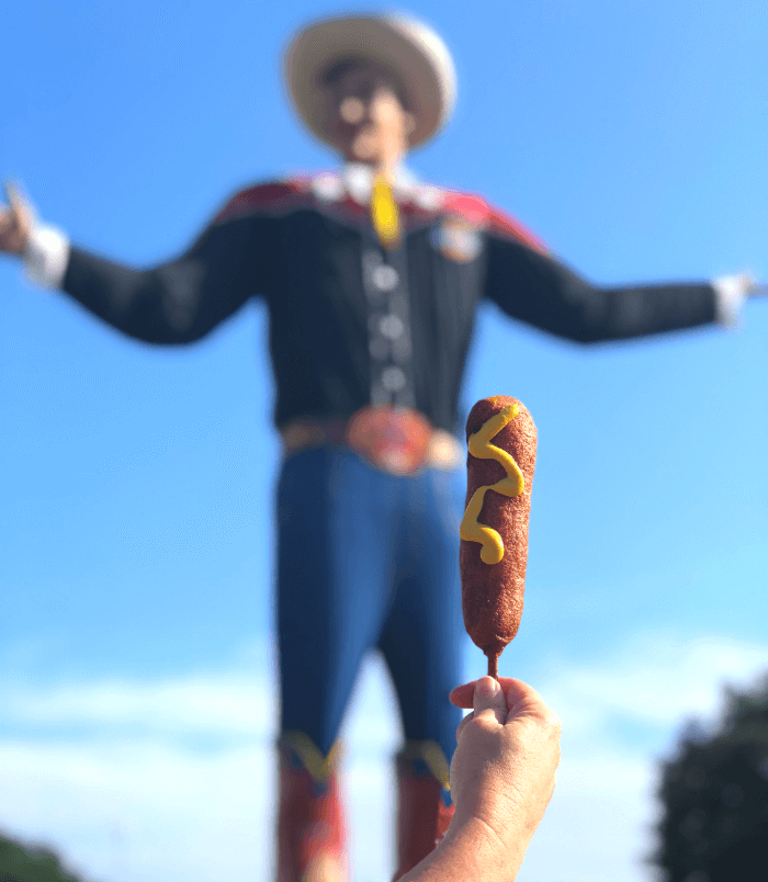 Hand holding a Fletcher's Corny Dog with mustard in front of Big Tex