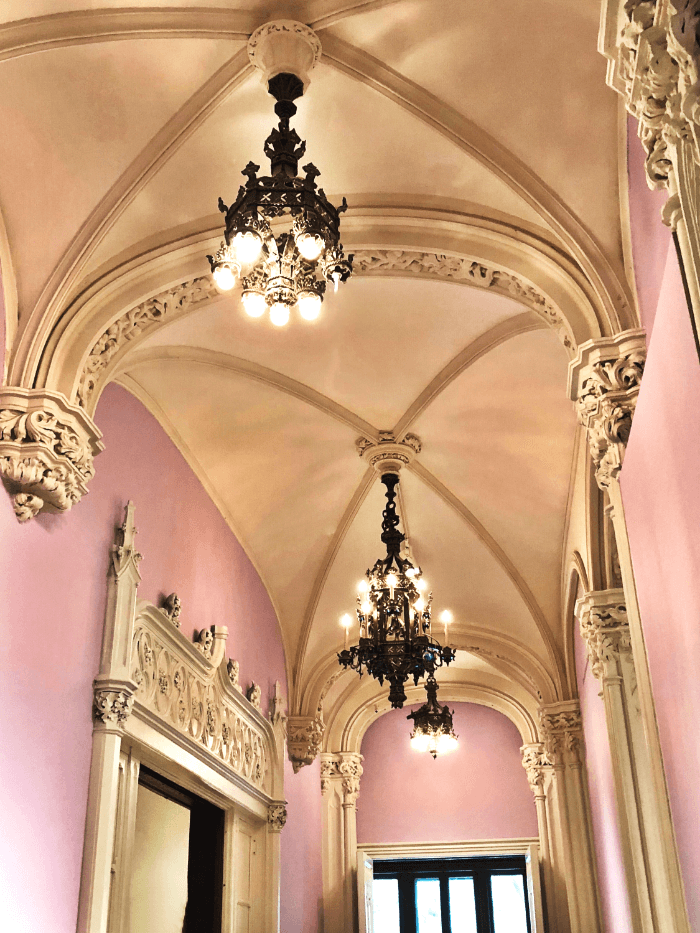 Interior hall of the Jewish Museum with pink walls and ornately carved moldings
