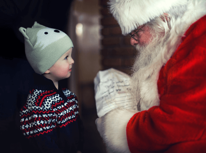 a little boy in a navy sweater and grey hat looking up at Santa