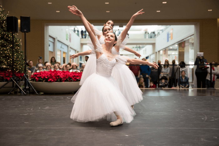 three ballerinas in light pink tutus posing in a shopping mall